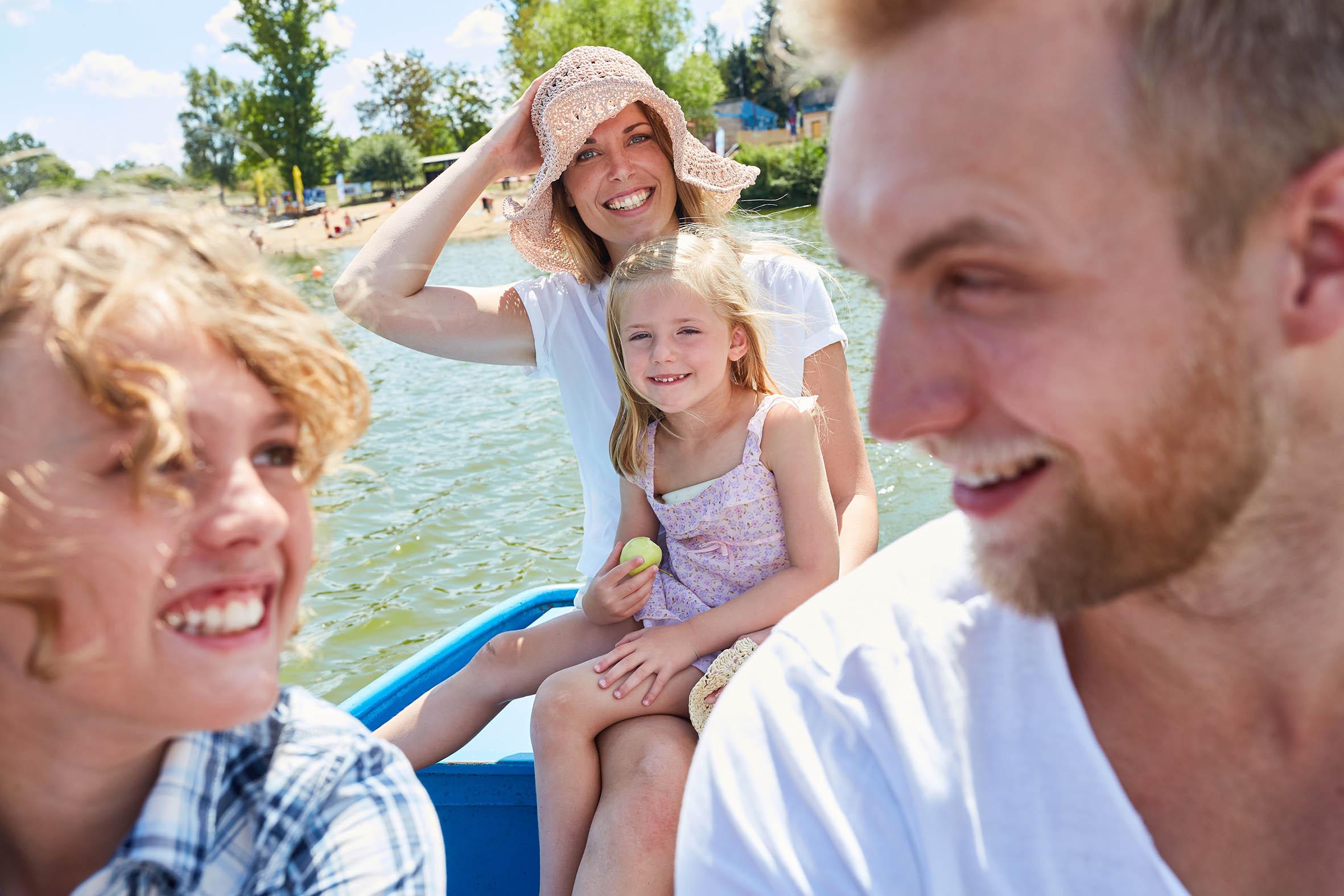 Familie mit Ruderboot auf See im Sommer auf dem Arendsee